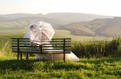 image of natal  - Bride and groom outside garden wedding on bench with African Natal Midlands mountain scenery background - JPG