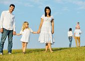 Two young families with kids walking on beautiful summer meadow enjoying and having fun