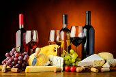 stock photo of brie cheese  - still life with cheese grapes red white and rose wine - JPG