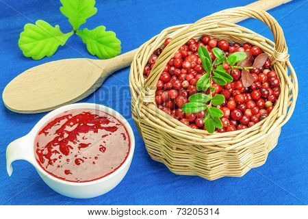 Fresh cranberries in basket with cranberry jam near