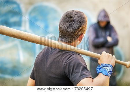 Aggressive teenager with a baseball bat against man at outdoor