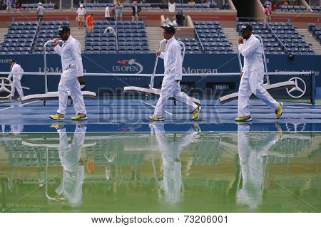 US Open cleaning crew drying tennis court after rain delay at Arthur Ashe Stadium
