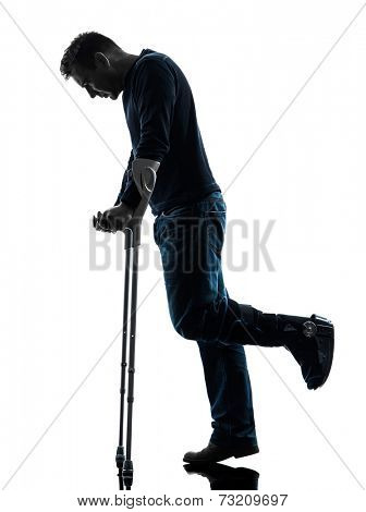 one man injured man walking sad with crutches in silhouette studio on white background