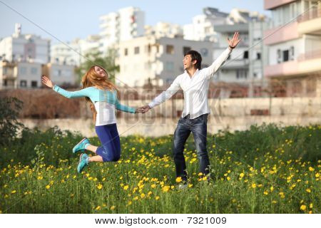 Young Couple Jumping In Meadow