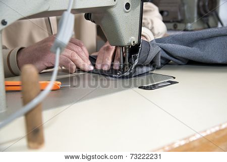 Tailor using industrial sewing machine with space for your text
