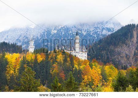Neuschwanstein Castle In Germany In Autumn With Clouds Covering The Mountains