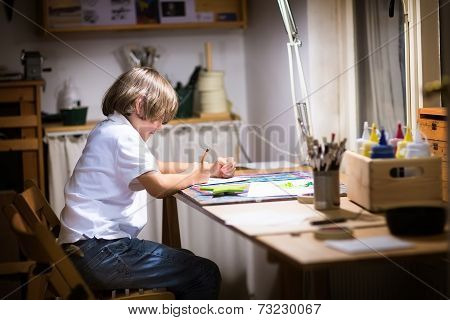 Little Boy Painting In Dark Room Late In The Evening