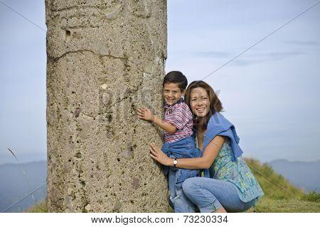 Hispanic mother and son hugging column, Oaxaca, Mexico