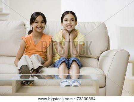 Hispanic sisters sitting on sofa