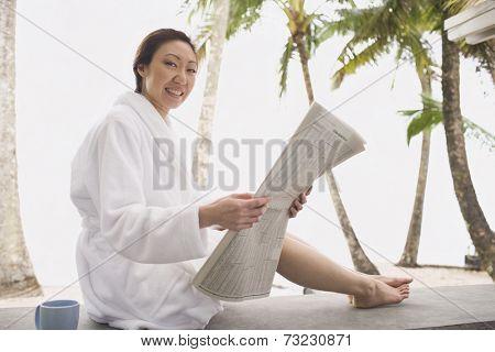 Asian woman in bathrobe reading newspaper
