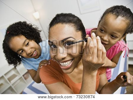 Mixed Race sisters watching mother apply mascara