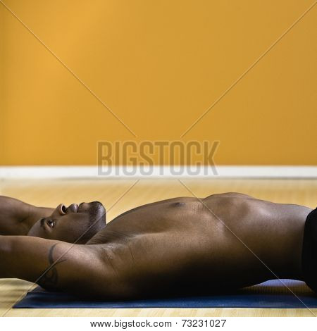 Bare-chested African man laying on yoga mat