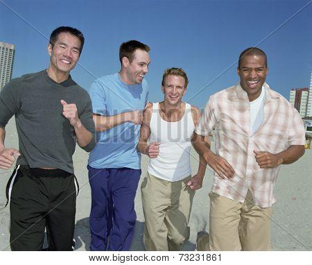 Multi-ethnic men running on beach