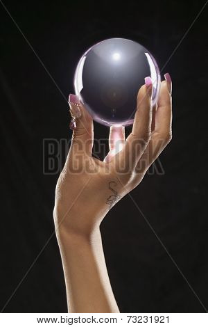 Indian woman's hand holding crystal ball