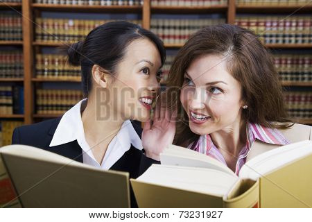 Multi-ethnic women whispering in law library