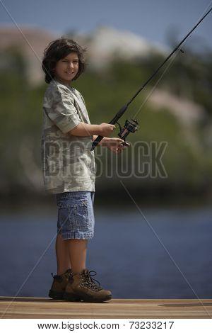Hispanic boy fishing on pier