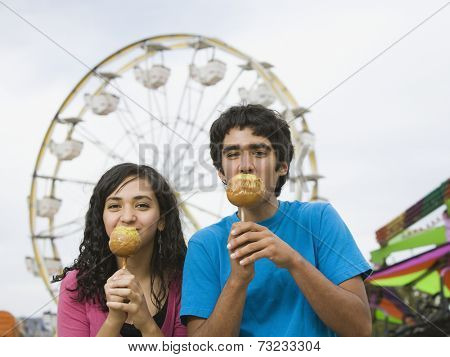 Multi-ethnic teenaged couple eating candied apples