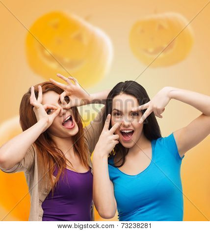 happiness, holidays, friendship and people concept - smiling teenage girls having fun over halloween pumpkins background