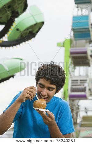 Mixed Race teenaged boy eating candied apple