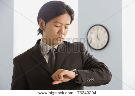 Asian businessman looking at wristwatch