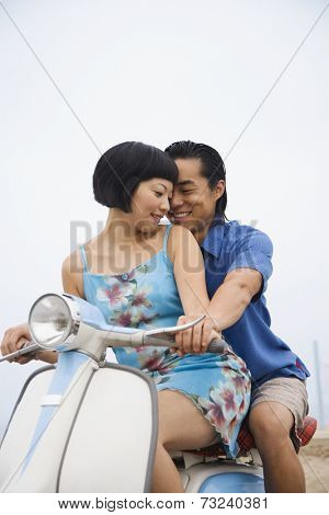 Asian couple sitting on motor scooter