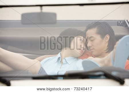 Asian couple hugging in convertible