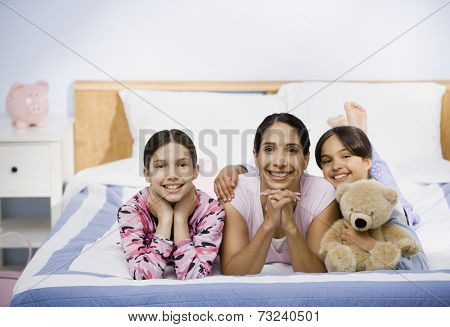 Hispanic mother and daughter laying on bed