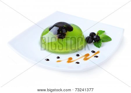 Green jelly with blackcurrant berries and sauce, isolated on white