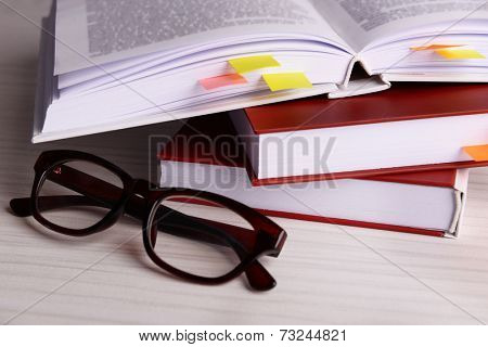 Books with bookmarks and glasses on wooden table