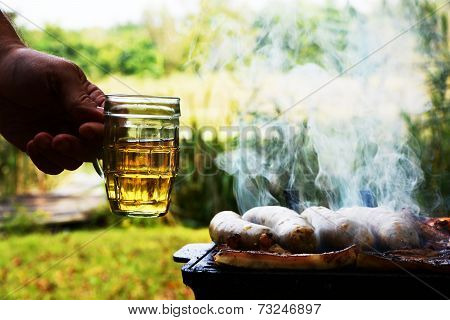 Male Hand With Mug Of Beer And Barbeque