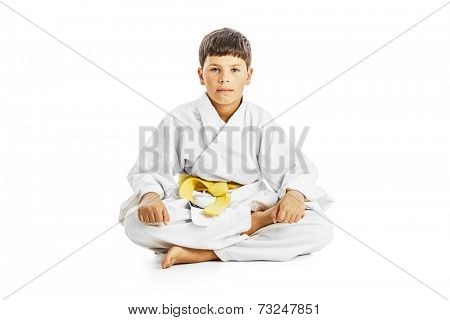 Little karate kid sitting legs crossed on white background