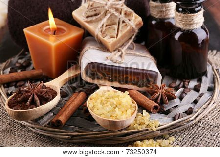 Organic soap with coffee beans, sea salt and milled coffee in wooden spoons on wicker mat, on wooden background, Coffee spa concept