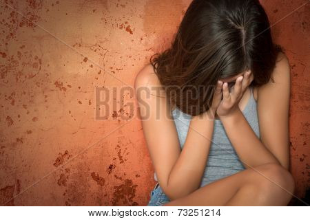 Beautiful teenage girl sitting on the floor crying