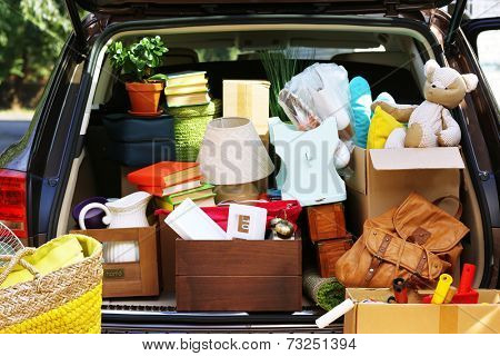 Moving boxes and suitcases in trunk of car, outdoors