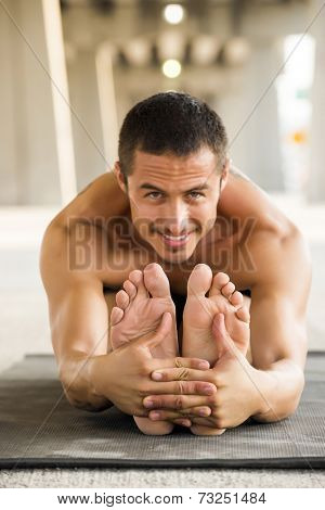 Man practicing yoga in a urban background (focus on the feet)