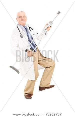 Full length portrait of a mature doctor playing guitar on a crutch isolated on white background
