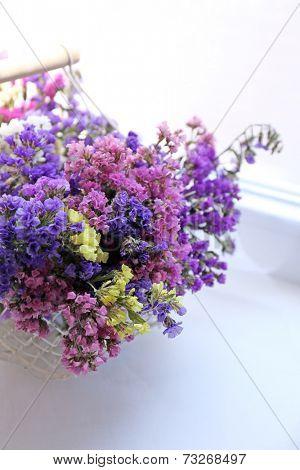 Beautiful flowers in basket on window background