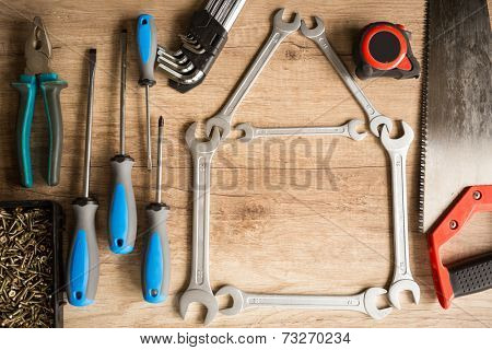 House of wrenches  and different tools on wooden background