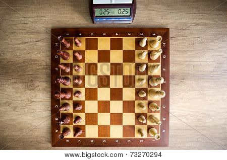 top view of  chessboard with chess and clock