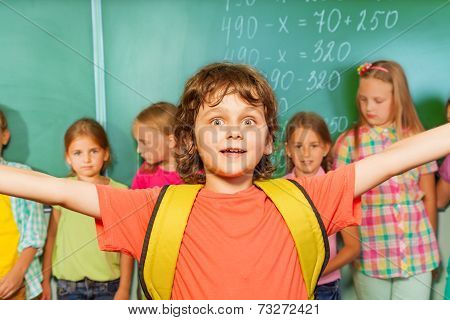 Excited boy with arms apart wears near chalkboard