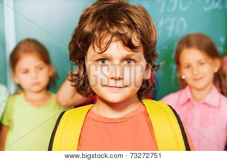 Portrait of boy with yellow bag near chalkboard