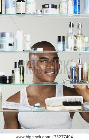 African man looking in medicine cabinet