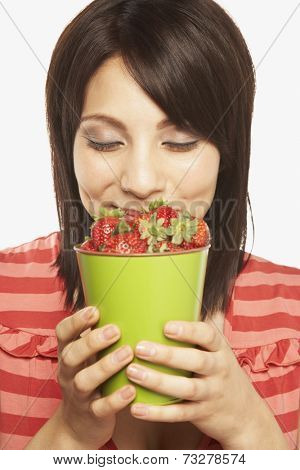 Hispanic woman smelling cup of strawberries