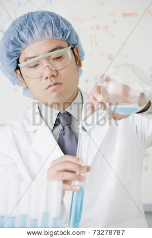 Asian male scientist filling vial