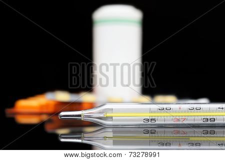 Mercury Thermometer And Pills On Black Background