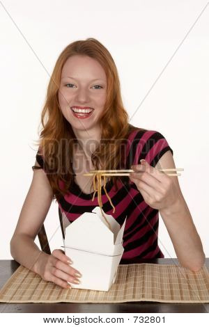 Red Head Woman with Chinese Noodles in Chopsticks