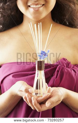Pacific Islander woman holding aromatherapy sticks
