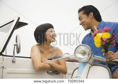 Asian man on motor scooter talking to woman in car