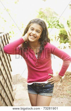Hispanic girl leaning on fence