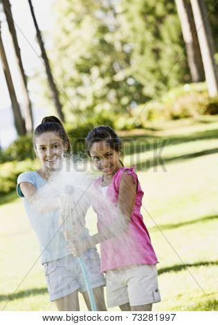 Hispanic sisters spraying hose
